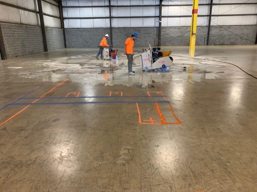 2 employees cutting concrete floor